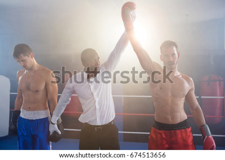 Referee lighting hand of winner standing with loser in boxing ring