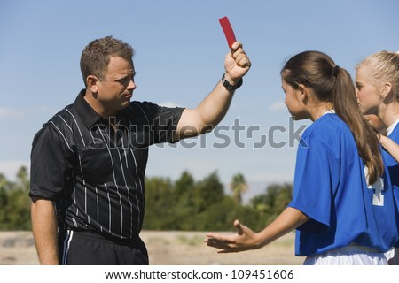 Referee showing red card to female soccer players