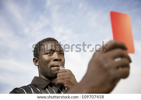 Referee whistles while holding a red card to a player
