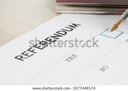 Referendum ballot paper, black pen, and passport on the table. Closeup