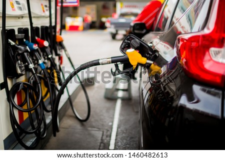 Refilling the car with fuel at the gas  station and blurry staff background,  refilling the car with fuel at the refuel station, the concept of fuel energy, Blurry image for background.