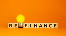 Refinance symbol. Wooden cubes with word 'refinance'. Yellow light bulb. Beautiful orange background. Business and refinance concept. Copy space.
