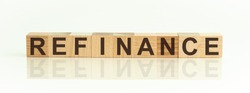 Refinance - word from wooden blocks with letters, front view on white background. Concept image.