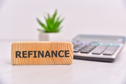 Refinance word on wooden block. Office table background.