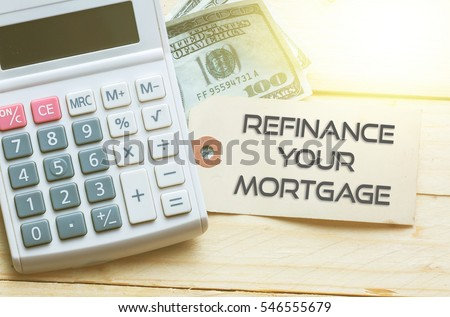 REFINANCE YOUR MORTGAGE Words on tag with dollar note and calculator on wood backgroud,Finance Concept