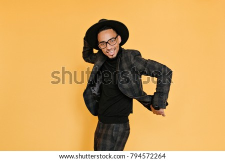 Refined african man having fun during photoshoot in studio. Indoor photo of smiling tall black guy in hat and glasses dancing on yellow background.