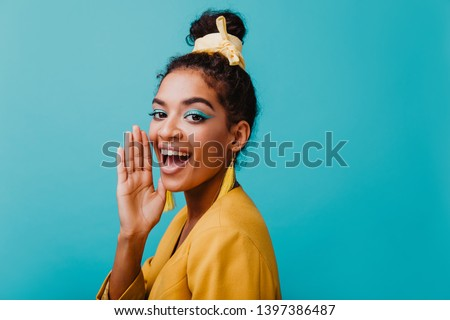 Refined black girl wears yellow earrings chilling during photoshoot. Studio portrait of joyful african lady with blue makeup.