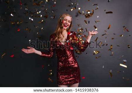 Refined caucasian girl in red dress dancing at party. Studio shot of cute blonde woman posing under confetti.