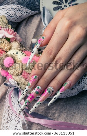 Refined painted long nails and hands with flower symbol. Easter or wedding theme with wreath rose and eggs. #363113051