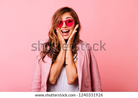 Refined white lady posing with surprised smile on rosy background. Gorgeous long-haired girl in funny pink glasses fooling around in studio.