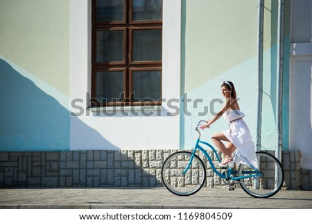 Refined woman is riding a blue vintage bike in a hot summer day in the city streets. Summer white dress develops a light breeze and an accessory on her head adds romanticism to the landscape #1169804509