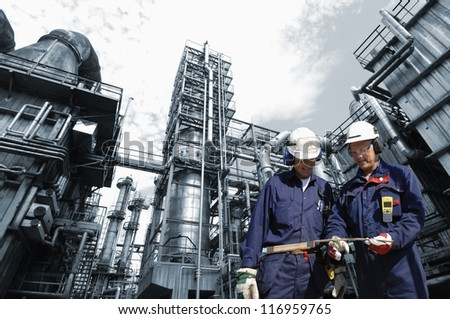 refinery engineers with large industry in background - stock photo