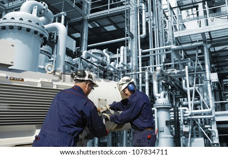 refinery workers inside large oil and gas installation