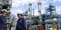 refinery workers inside large oil and gas petrochemical refinery