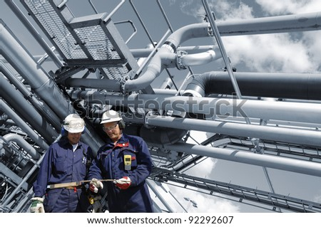 refinery workers with pipeline construction in background