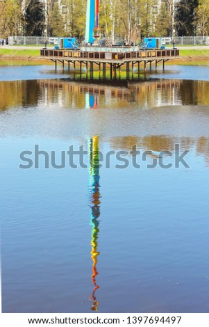 reflected reflection of tower attraction in an amusement park multicolored rainbow colors in lake #1397694497