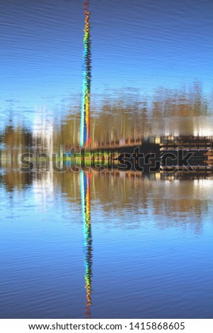 reflected reflection of tower attraction in an amusement park multicolored rainbow colors. Soft selective focus #1415868605