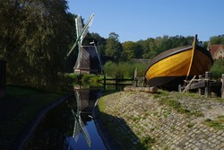 Reflected windmill on lake next to traditional boatyard in Netherlands.