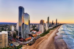 Reflecting facets of modern urban high-rise towers on Australian Gold Coast in Queensland Surfers Paradise. Wide sandy long beach of Pacific shore at sunrise in elevated aerial view along waterfront.