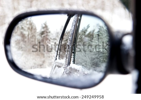 Reflecting of winter forest in a rear view car mirror