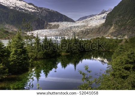 Reflecting pine trees in the foreground of the Mendenhall Glacier in Juneau, Alaska.