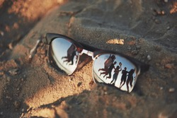 Reflecting sunglasses on a sandy beach in the summer, and the blue sky with people is reflected in glasses