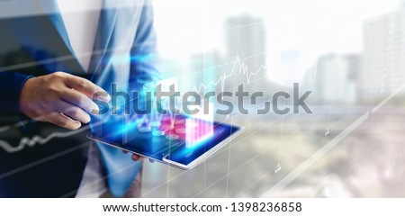 Reflection Businessman using tablet analyzing data and economic growth graph chart and copy space. Concept on tablet with hologram. #1398236858