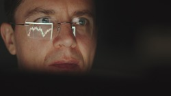 REFLECTION: Face of trader in an eyeglasses looking a graphs in a the night