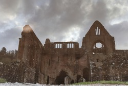 reflection in a puddle of an old ruined abbey, built in stone, cloudy sky