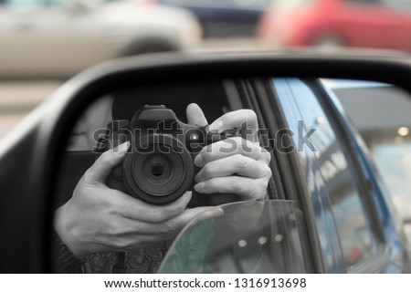 Reflection in side view mirror of someone with DSLR camera. Hidden photographing, paparazzi concept