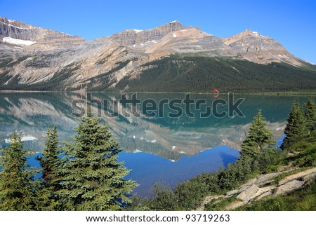 Reflection in smooth water of mountain lake (Banff National Park, Alberta, Canada)