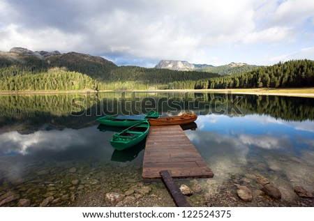 Reflection in smooth water of mountain lakes and boats