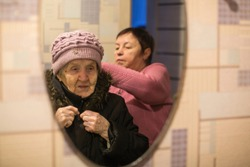 Reflection in the mirror, a woman helps put on her old mother's coat.