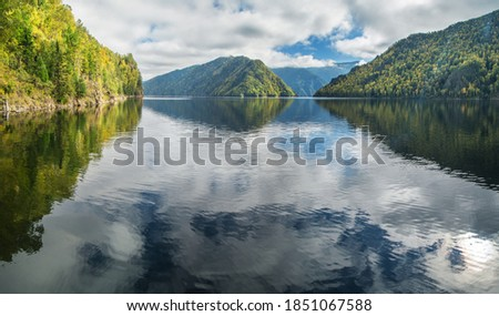 Photo of  Reflection in the water of the mountains and sky. The calm flow of the Yenisei River in Siberia. Autumn view.