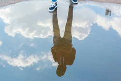 Reflection in water of man with casual style standing in bright blue sky