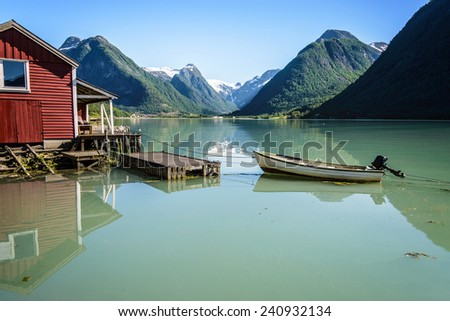 Reflection of a boat, a jetty, a red boathouse and mountains in the tranquil water of Fj�¦rlandsfjord, part of the Sognefjord in the village of Fj�¦rland or Mundal, Sogn og Fjordane, Fjord Norway.