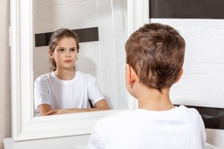 Reflection of a boy in the mirror by a girl. Sister and brother concept. Boy and girl. Concept of Gender dysphoria.