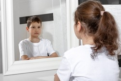 Reflection of a girl in the mirror by a boy. Sister and brother concept. Boy and girl. Concept of Gender dysphoria.