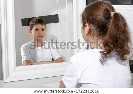 Reflection of a girl in the mirror by a boy. Sister and brother concept. Boy and girl. Concept of Gender dysphoria. Сток-фото ©