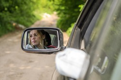 Reflection of a girl sitting in the car in a car mirror