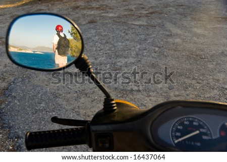 Reflection of a hiker on a Mediterranean beach in a motorcycle mirror.