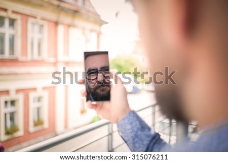 Reflection of a man\'s face in mobile phone