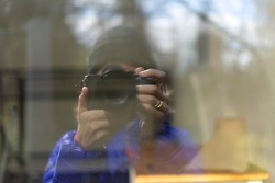 Reflection of a photographer in the glass