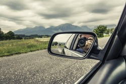 Reflection of a photographer with a camera in the rear view mirror of a car in nature.