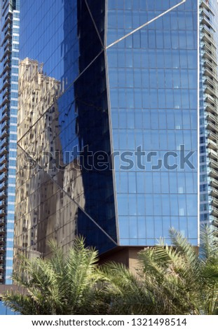 Reflection of a skyscraper in the facade of a skyscraper - and trees (Dubai UAE) #1321498514