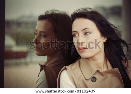 reflection of a young dark-haired girl in a shop window