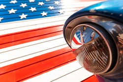 Reflection of American flag in the headlight of a classic car on route 66 america's iconic highway