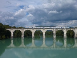 reflection of an arched bridge with train in deep blue water