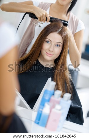 Reflection of beautician doing hair style for woman in hairdresser\'s. Concept of fashion and beauty