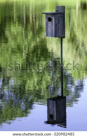 Reflection of birdhouse in pond by trees #320982485